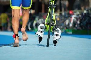 Triathlet mit rennt mit Fahrrad in Wechselzone