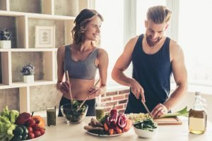 attraktives sportliches paar macht gesundes essen in küche