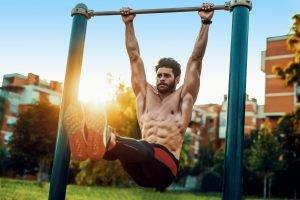 mann mit sixpack macht beinheben an klimmzugstange im freien