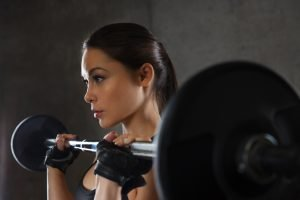 frau trainiert mit wenig gewicht mit langhantel