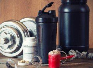 supplements portioniert neben eiweißshaker, symbolbild muskelaufbau ernährung