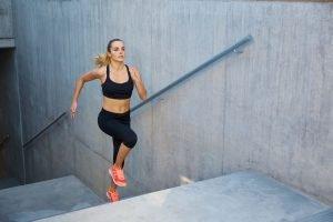 Frau joggt eine Treppe hoch