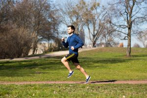 Mann joggt im Park und treibt Cardio-Training