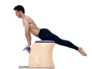 mann macht pilates auf dem gerät chair