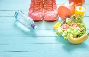 sportschuhe obst orangensaft wasser hantel obst und gemüse auf blauen holzdielen