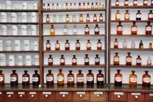 fläschchen und dosen im holzregal einer traditionellen apotheke