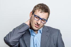 mann mit muskelschmerzen im nacken durch büroarbeit