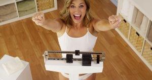 frau auf waage freut sich über schnellen gewichtsverlust