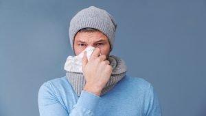 mann mit grippe hält sich taschentuch an die nase