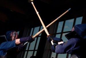 zwei kendo kampfsportler kämpfen mit stöcken