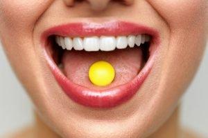 offener mund einer frau mit gelber fatburner pille auf zunge