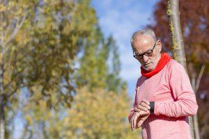 alter läufer guckt auf pulsuhr symbolbild maximale herzfrequenz