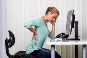 frau mit rückenschmerzen bei der arbeit
