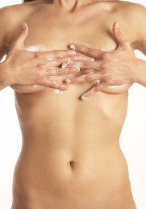 frau mit nacktem oberkörper cremt sich die brüste ein