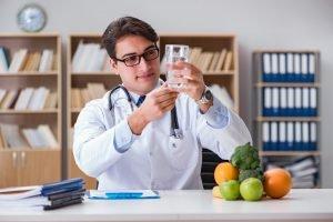 ernährungsberater sitzt mit gesunden lebensmitteln an tisch