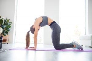 frau macht buckel auf fitnessmatte