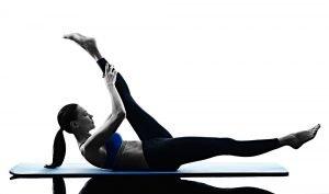 frau macht übung auf gymnastikmatte