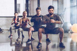 männer und frauen machen squats mit gewichten beim boxtraining