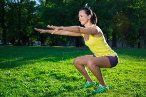 frau trainiert mit kniebeugen die beine