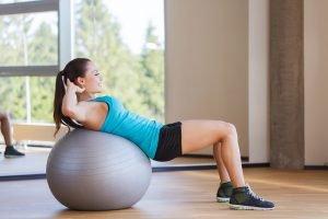 frau macht zuhause übung auf gymnastikball