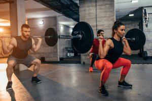 männer und frau machen kniebeugen mit viel gewicht