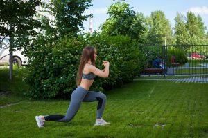 Frau macht Lunges im Garten