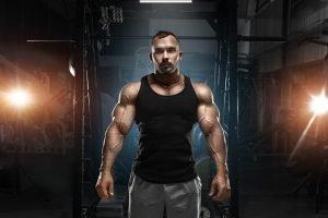 Mann mit massiven Muskeln in Fitnessstudio