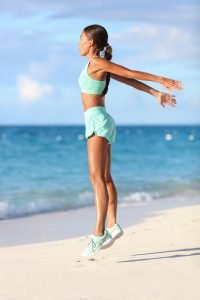 Frau macht Burpees zum Abnehmen am Strand