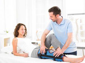 Patient mit Orthopädie Schiene am Knie neben Physiotherapeut
