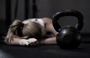 frau liegt nach crossfit workout am erschöpft am boden