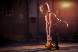 frau macht squats mit ketllebell