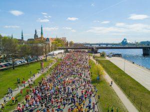 sehr viele läufer auf breiter straße neben einem fluss