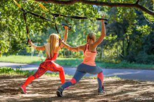 zwei frauen bei sling training in wald