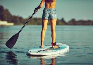Frau beim Stand-Up-Paddeln auf einem See