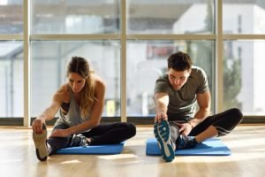 mann und frau dehnen beine auf matte in fitnesstudio