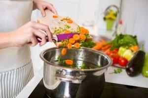 frau kocht frische suppe
