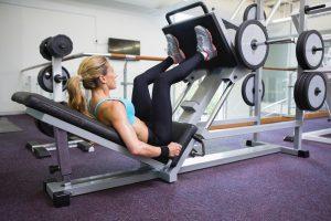 frau beim training an einer beinpresse im fitnessstudio