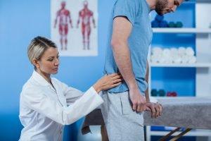 ärzting untersucht patient im bereich unterer rücken