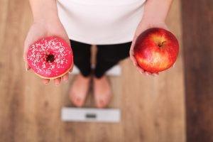 frau auf waage mit donut und apfel in der hand
