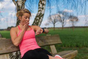 frau gähnt und guckt dabei auf fitnesstracker