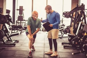 alter mann dehnt sich neben fitnesstrainer in fitnessstudio