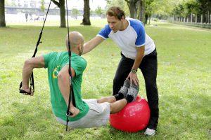 mann trainiert mit personal coach auf wiese