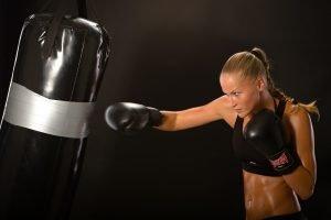 durchtrainierte frau beim boxtraining mit boxsack
