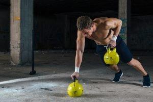 mann trainiert schulter mit kettlebells