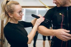 frau legt ems fitness trainingsweste bei mann an