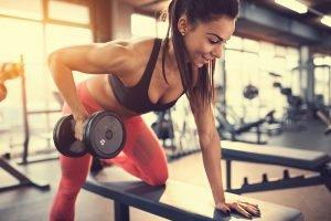 Frau trainiert mit Kurzhantel im Fitness-Studio