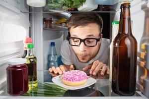 mann starrt auf donut in kühlschrank