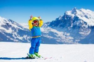 kind auf skiern jubelt