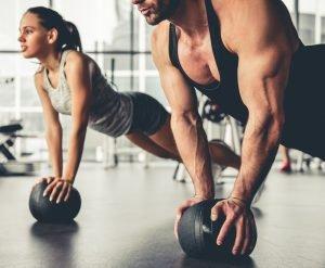 frau und mann beim plank mit gymnastikball