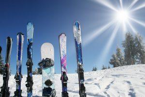 mehrere paar ski und snowboard im schnee